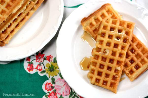Homemade waffles on a plate with butter and syrup.