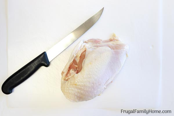 Knife and chicken on board for how to debone chicken breast