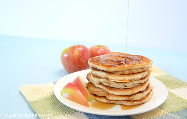 the prepared apple pancake recipe stack of pancakes with syrup pouring on them.
