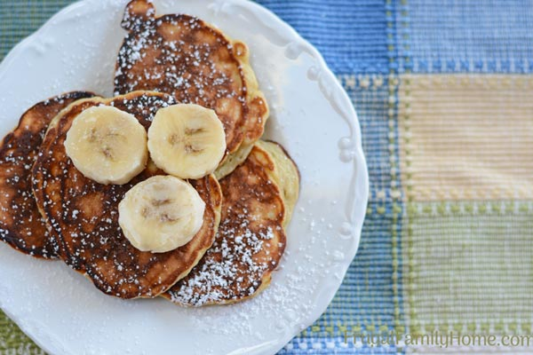 The easy banana pancakes on a plate ready to serve with bananas on top.