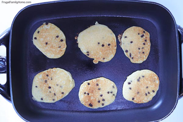Chocolate Chip pancakes cooking in a pan.