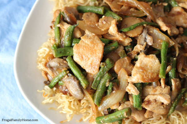 A plate of stir fried chicken and green beans.