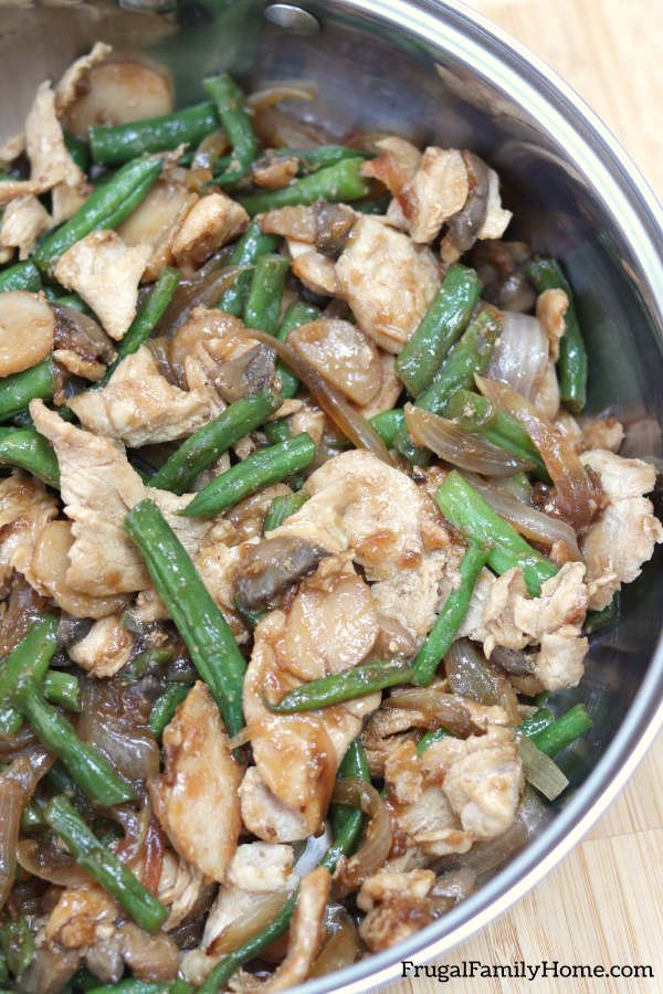 chicken and green beans in a skillet cooked for dinner.